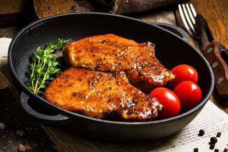 Grilled pork chops in sweet honey glaze, served in grill iron skillet with fresh thyme, rye bread and cherry tomatoes, close up. Selective focus Stock Photo