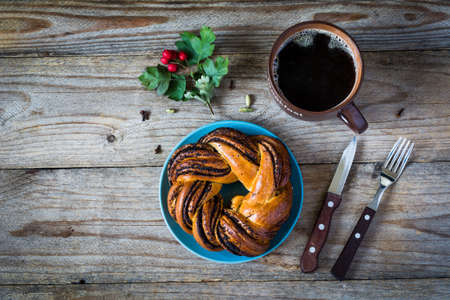 cinnamon swirl: Pastry and coffee on wooden table, top view