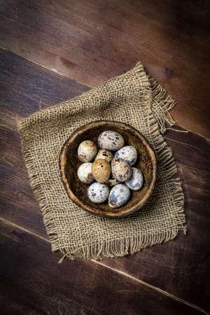 Fresh organic quail eggs in ceramic bowl on linen rag. Natural light, selective focus, top view