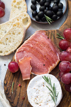 mediterranian: Italian appetizer plate: cured meat, cheese, grapes, olives and fresh bread. Top view