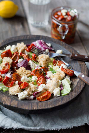 Panzanella salad with roasted tomatoes and feta cheese, closeup view, selective focus
