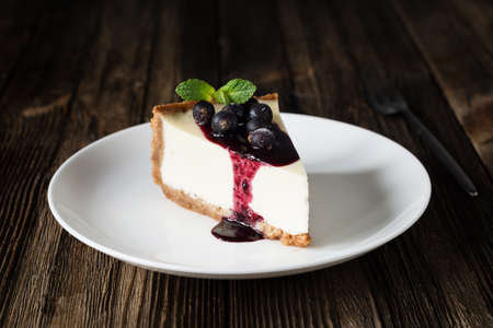 Piece of cheesecake with black currant and blueberry sauce on a white plate on a wooden table. Closeup view