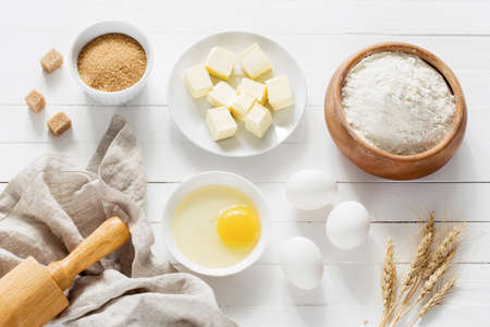 Baking ingredients on white table. White eggs, rolling pin, flour, sugar and spices. Home baking concept baking cake or cookies ingredients