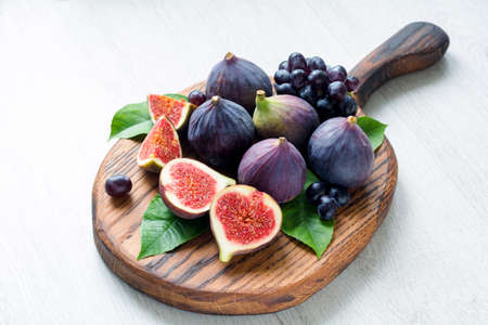 Fresh figs and grapes on white background. Snack set for cheese and wine