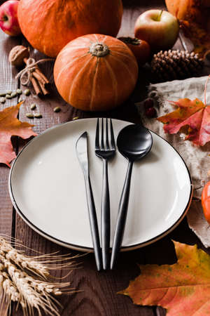 Thanksgiving dinner table setting with pumpkins, wheat, fallen leaf and black cutlery. Vertical composition, selective focus Stock Photo