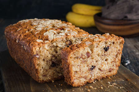 Homemade banana bread loaf with walnuts sliced on wooden cutting board. Closeup view, horizontal
