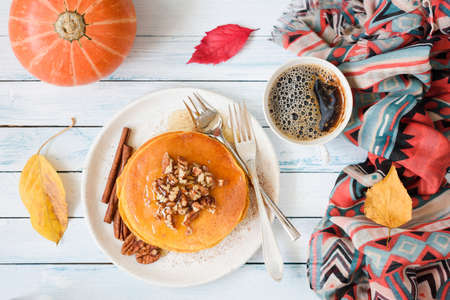 Pumpkin pancakes with pecan nuts, honey and cup of coffee. Autumn food composition on white table. Top view, flat lay composition 版權商用圖片