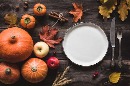 Autumnal table setting for Thanksgiving dinner. Empty plate, cutlery, pumpkins, apples and spices on wooden table. Fall food concept Standard-Bild