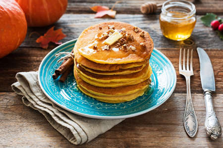 Pumpkin pancakes with pecan nuts, butter and honey on a blue plate. Seasonal autumn food