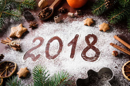 christmas backgrounds: New Year 2018 written on flour and Christmas Decorations Gingerbread cookies, cinnamin, oranges, spices, nuts and cookie cutters on wooden background. Christmas card, New Year greeting card Stock Photo