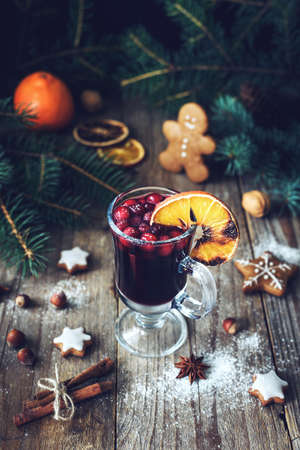 christmas backgrounds: Mulled wine in glass with cranberries and spices decorated with burnt orange. Christmas drink. Holiday food concept