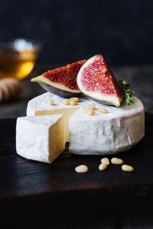 Brie, camambert cheese, fresh purple figs, nuts and honey on dark wooden backdrop. Closeup view, vertical