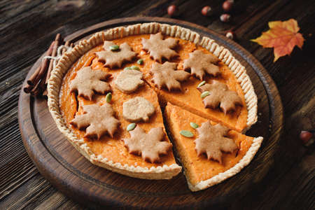 Homemade Pumpkin pie decorated with gingerbread cinnamon cookies on wooden table with a slice cut out. Whole pumpkin pie Stock Photo