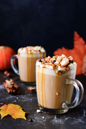 Pumpkin spice latte with whipped cream, caramel sauce and chocolate bars on black backdrop. Vertical, copy space for text. Autumn comfort food