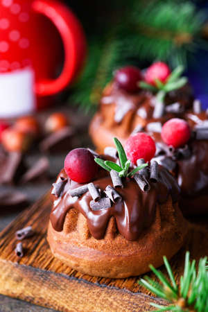 Chocolate mini budnt cakes decorated with chocolate glaze, swirls, cranberries and rosemary. Sweet Christmas food. Closeup view