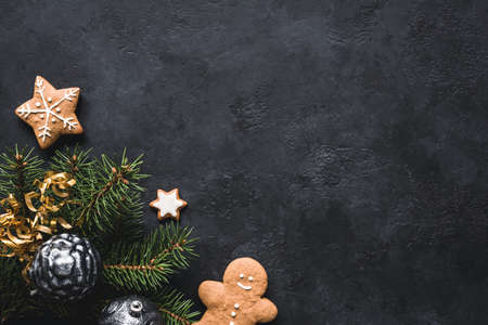 Christmas background. Gingerbread cookies, fir tree, christmas toys and holiday decorations frame on blackboard or stone backdrop. Top view with copy space for text Фото со стока