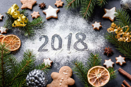 Happy New Year 2018 greeting written on flour. Gingerbread cookies, spices, fir tree and Christmas toys around. Christmas, New Year winter holidays greeting card.