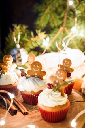 Gingerbread cupcakes, gingerbread cookies and Christmas lights. Closeup view, selective focus