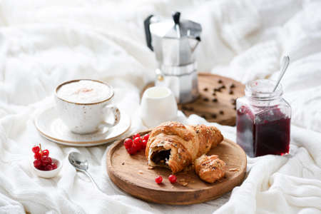 Croissant with chocolate filling, cup of coffee and jam on a tray. Italian steam coffee maker on background. Breakfast in bed. Continental breakfast