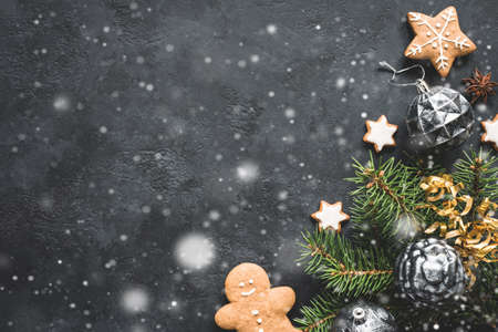 Stylish Christmas background with falling snow, vintage Christmas toys, fir tree and cookies on black stone background. Top view, copy space for text.