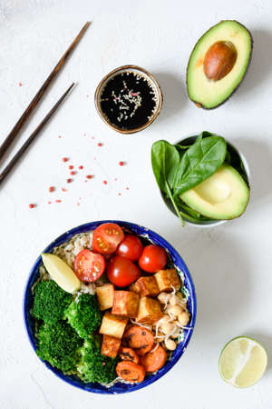 Buddha bowl with roasted carrots, avocado, tomato, broccoli, sprouts and tofu cheese. Vegetarian bowl. Top view on white concrete background Stock Photo