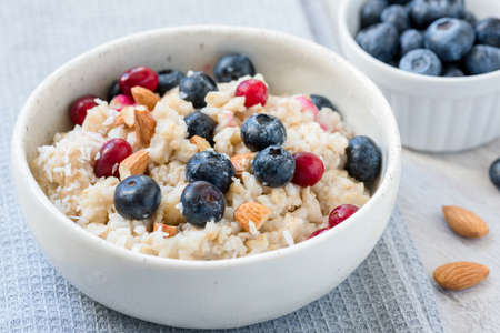 Oatmeal porridge with blueberries, cranberries and almonds in white bowl. Closeup view. Concept of healthy eating, dieting, healthy lifestyle