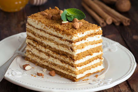 Honey layer cake Medovik decorated with mint leaf and almonds. Russian honey cake. Closeup view