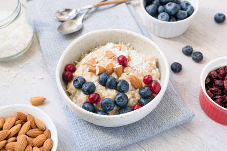 Oatmeal porridge bowl wtih blueberries, cranberries, almonds and coconut. Healthy breakfast, healthy eating concept