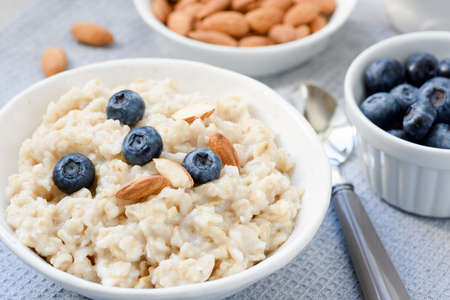 Coconut oatmeal porridge with blueberries and almonds. Closeup view. Healthy eating, dieting, healthy breakfast food