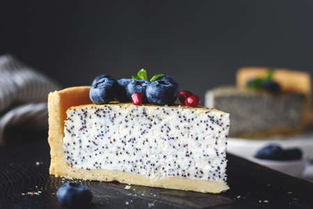 Cheesecake with poppy, blueberries and mint leaf on dark cutting board. Closeup view. Toned image Фото со стока