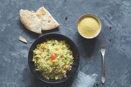 Tabbouleh with cous cous and arabic flatbread on concrete background. Healthy dietetic meal. Table top view Фото со стока