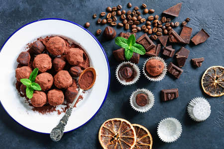 Dark chocolate truffles, coffee beans, fresh mint leaf and dark chocolate pieces on stone background. Table top view Фото со стока