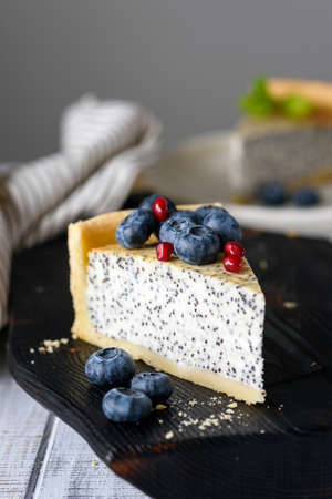 Slice of cake with poppy and blueberries. Closeup view, selective focus. Toned image Фото со стока