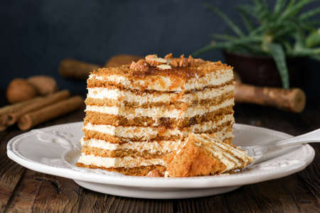 Honey cake with almonds on white plate. Russian cake Medovik Фото со стока