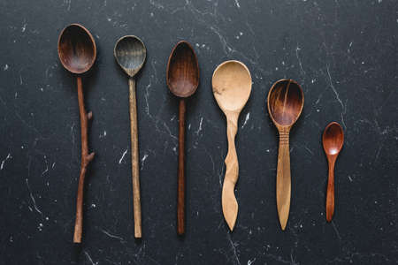 Old wooden spoons on dark background. Top view