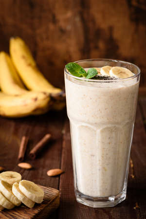 Banana smoothie in tall glass on wooden background. Healthy nutritious vegan drink, power boost, fitness, dieting food. Concept of healthy eating, dieting, weight loss