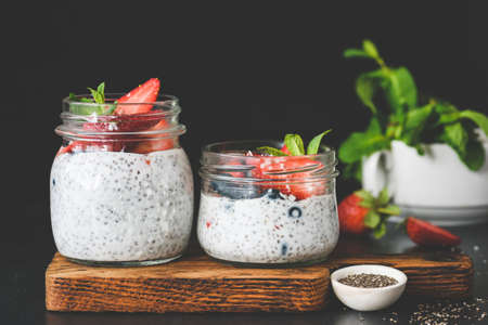 Chia pudding with fresh strawberries and blueberries decorated with mint leaf on dark background. Copy space for text. Concept of healthy eating, dieting, healthy lifestyle and clean eating