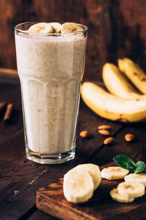 Banana smoothie in glass on brown wooden table. Healthy food, healthy eating concept