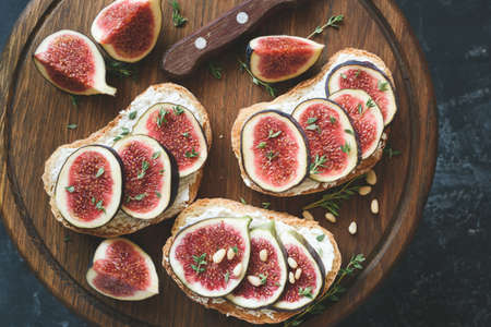 Fig and goat cheese toasts on wooden cutting board. Top view Фото со стока