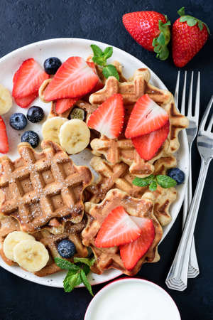 Belgian waffles with fresh strawberries, blueberries and banana. Top view. Healthy breakfast concept