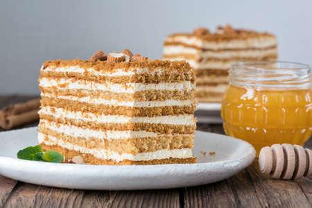 Honey cake Medovik on white plate. Russian cake. Layered biscuit cream cake 스톡 콘텐츠