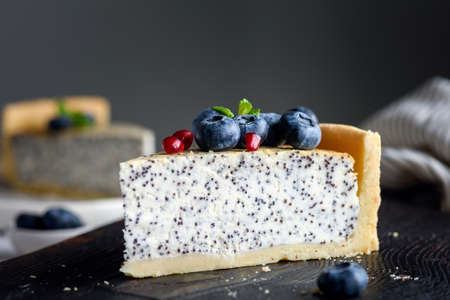 Slice of cheesecake with poppy seeds decorated with fresh blueberries, pomegranate seeds and mint. Selective focus