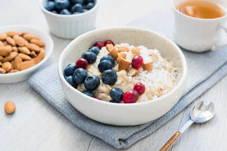 Oatmeal porridge bowl with blueberries, cranberries and almonds and cup of green tea. Concept of healthy lifestyle, healthy eating, fitness menu and dieting