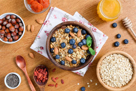 Healthy lifestyle breakfast with granola, honey, oats, superfoods and chia seeds. Dieting, healthy eating, weight loss concept. Table top view Фото со стока