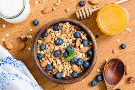 Granola bowl with blueberries, almonds and honey on wooden table. Top view
