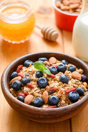 Granola with dried fruits, nuts and fresh blueberries in wooden bowl. Healthy lifestyle, healthy breakfast, dieting and weight loss concept Фото со стока