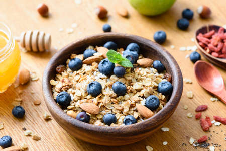 Homemade granola in wooden bowl with fresh blueberries. Healthy foods, superfood, healthy lifestyle, dieting, weight loss concept. Selective focus