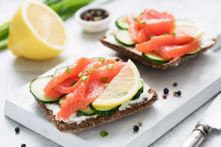 Rye bread with smoked salmon, cream cheese and cucumber on white cutting board. Healthy appetizer Фото со стока