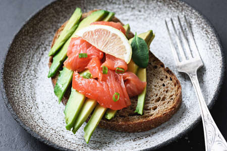 Sandwich with smoked salmon and avocado on plate. Selective focus
