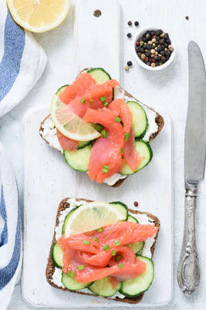 Smoked salmon, cream cheese and cucumber toast sandwiches on white. Top view Фото со стока